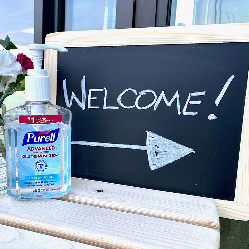"A ""welcome"" sign and hand sanitizer await beer takeout buyers and those picking up food donations"