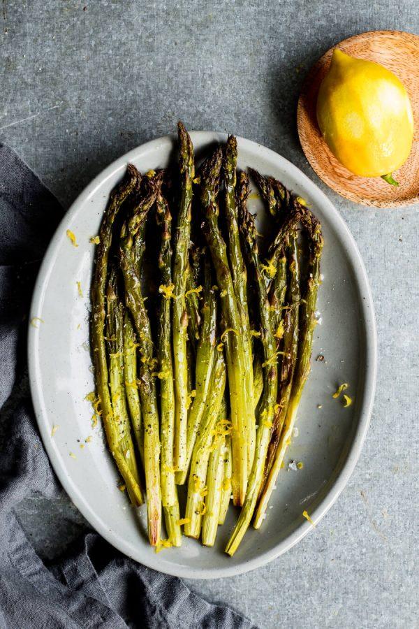 roasted asparagus on a plate with lemon zest