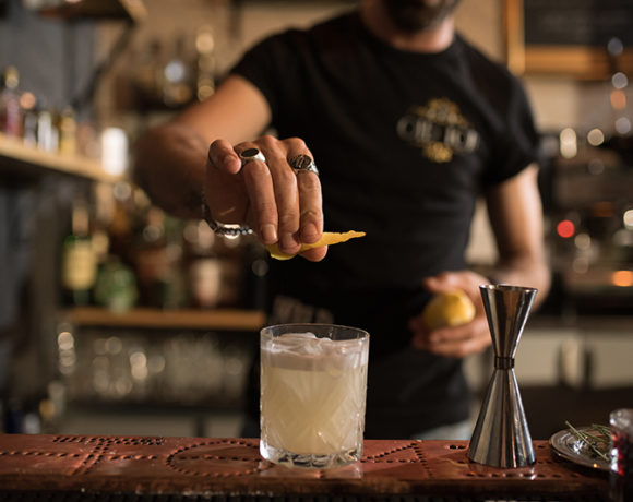 bartender spritzing lemon on a drink