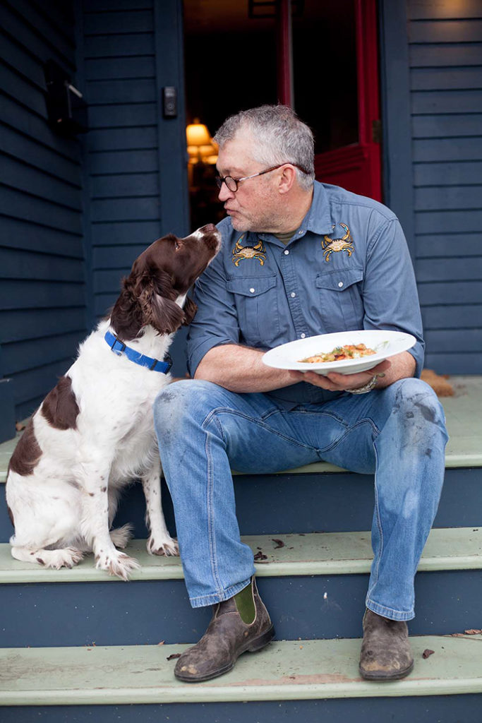 Phillip Hammonds with his dog and a bowl of shrimp and grits