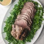 vitello tonnato on a platter with arugula
