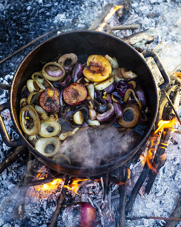 fruit in a cast iron pan cooking on hot coals