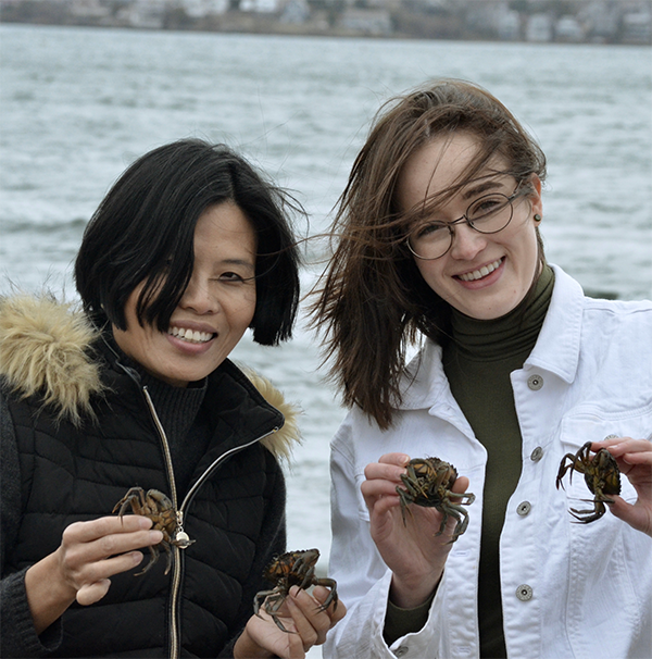 women holding green crabs