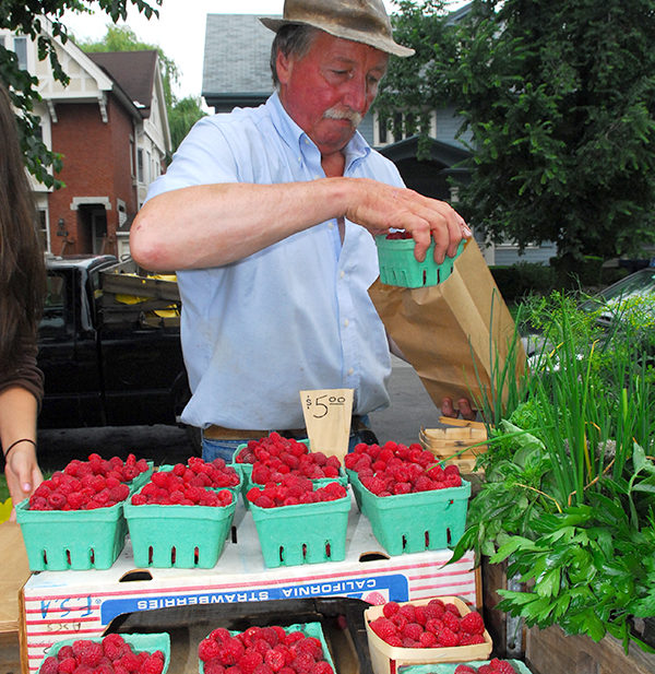 Farmers market vendor with raspberries