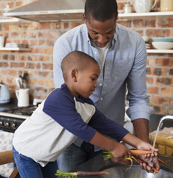 Son Helping Father To Prepare Vegetables
